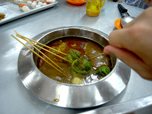 You dip the sticks into the bubbling sauce to cook it. You pay for the number of sticks eaten.